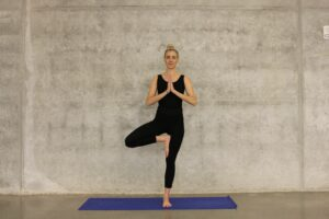 woman in black attire doing one foot stance yoga